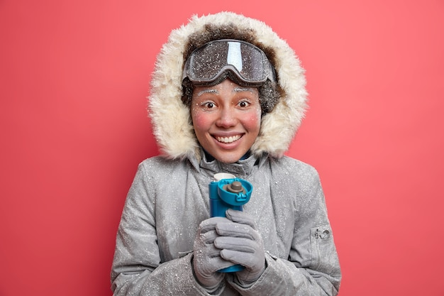 Positieve vrouw besteedt tijd buiten tijdens ijzig weer drinkt warme drank uit thermos glimlacht graag gekleed in bovenkleding.