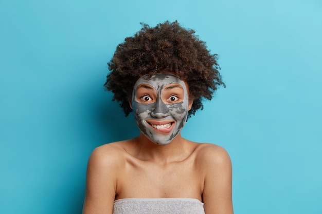 Positieve vrouw bijt lippen geniet van ochtendhygiëneprocedures past gezichtskleimasker toe om de huid te verjongen maakt gebruik van natuurlijk cosmetisch product dat over blauwe muur wordt geïsoleerd