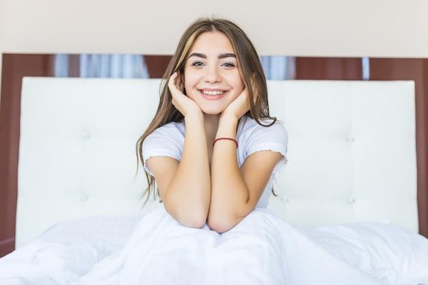 Positieve vrouw die in bed zit en thuis naar de camera glimlacht