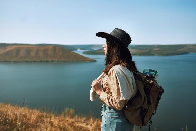 Positieve vrouw die in cowboyhoed bij bakota-gebied loopt