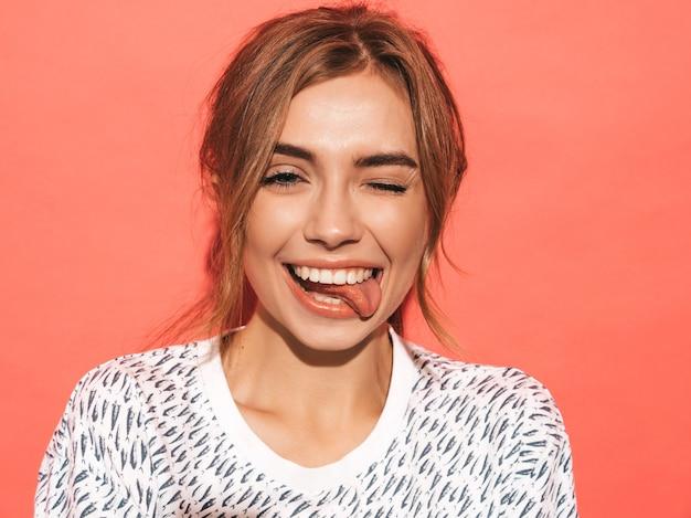 Positieve vrouw die lacht. het grappige model stellen dichtbij roze muur in studio. toont tong en knipoogt