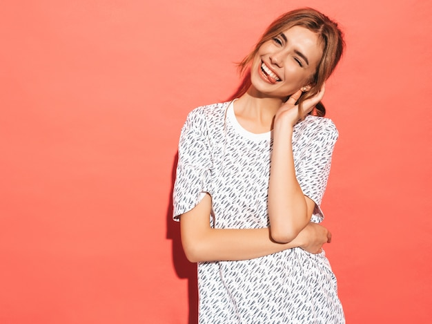 Positieve vrouw die lacht. het grappige model stellen dichtbij roze muur in studio. toont tong