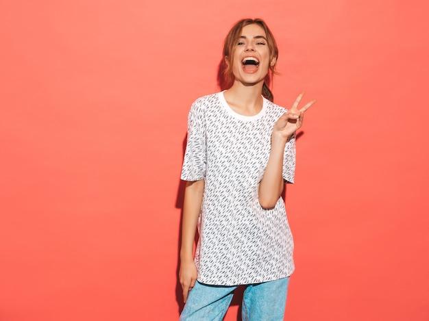 Positieve vrouw die lacht. het grappige model stellen dichtbij roze muur in studio. toont vredesteken