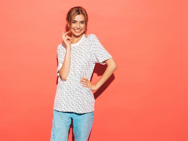Positieve vrouw die lacht. het grappige model stellen dichtbij roze muur in studio