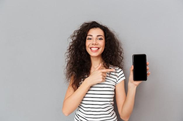 Positieve vrouw die met kaukasische verschijning wijsvinger zoals reclame van haar smartphone het stellen tegen grijze muur richten