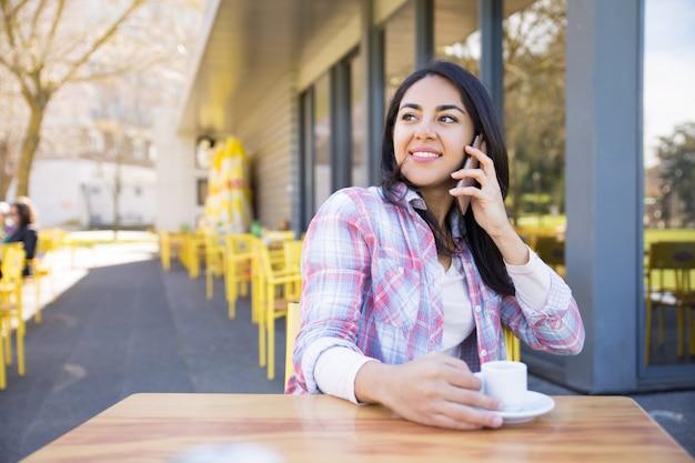 Positieve vrouw die op telefoon en het drinken koffie spreekt