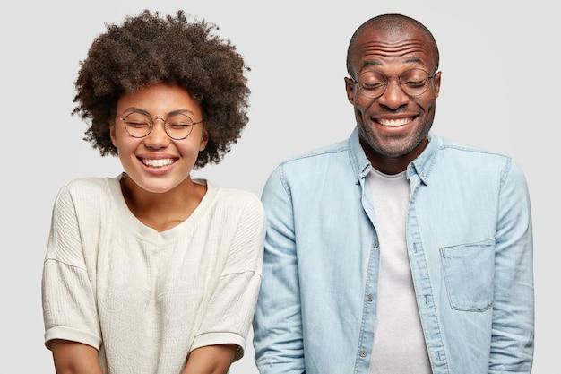 Positieve vrouw en man hebben tevreden uitdrukkingen, blij zijn met goed nieuws