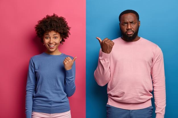 Positieve vrouw en nors, ontevreden man wijzen naar elkaar, geven de schuld of stellen voor om voor hem of haar te kiezen, draag blauwe en roze kleding