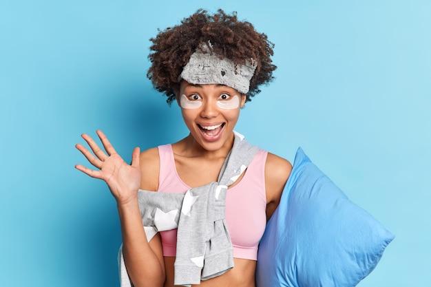 Positieve vrouw heft palm op, blij dat ze rust heeft na zware week geniet van luiheid en ontspanning houdt palm omhoog houdt kussen geïsoleerd over blauwe muur opgewonden met goede dromen