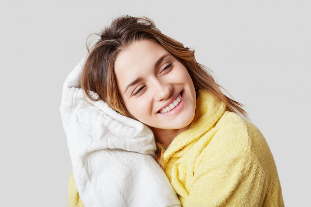 Positieve vrouw in badjas, houdt witte handdoek, rust na het nemen van alleen showr, heeft een vrolijke uitdrukking