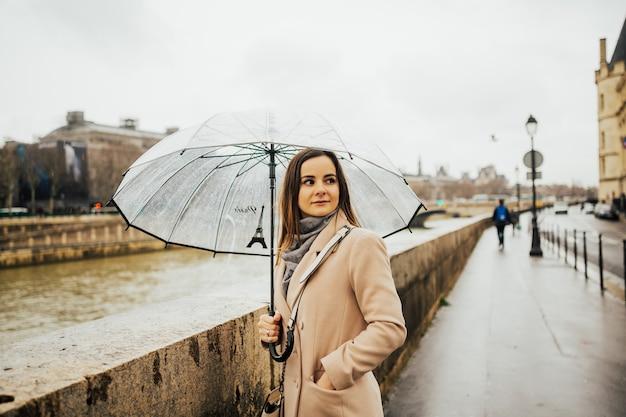 Positieve vrouw in beige jas staande in straat onder grote transparante paraplu, tijdens grijze regenachtige dag.