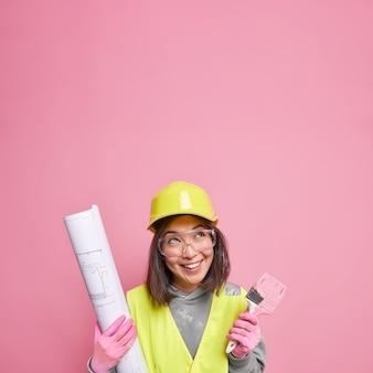 Positieve vrouw in beschermende helm en uniform houdt blauwdruk kwast vast en kijkt naar boven met vrolijke uitdrukking introduceert bouwproject