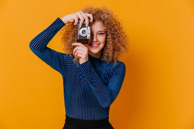 Positieve vrouw in gestreepte blauwe trui neemt foto op retro camera op gele ruimte.