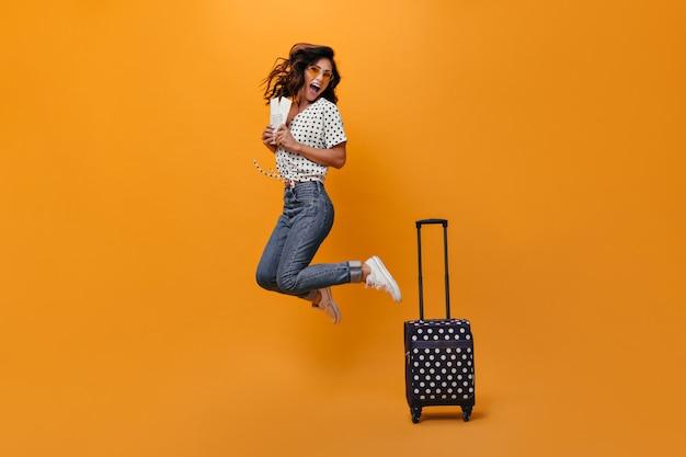Positieve vrouw in glazen springt op oranje achtergrond met kaartjes voor vakantie. blije volwassen vrouw in zonnebril en zwarte stipblouse verheugt zich bij camera.