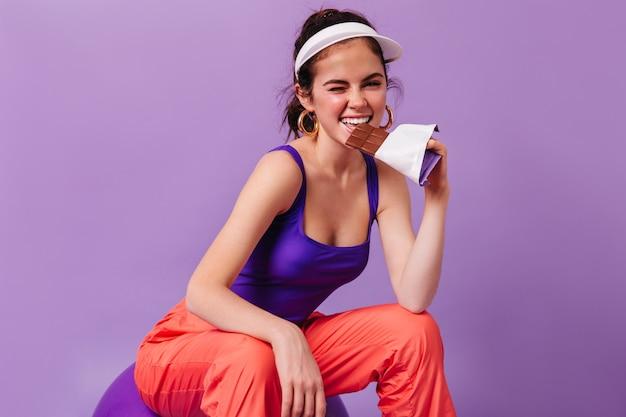 Positieve vrouw in goed humeur bijt chocolade