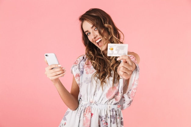 Positieve vrouw in jurk met smartphone en creditcard, geïsoleerd op roze