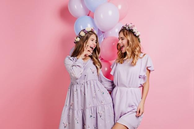 Positieve vrouw in lange paarse jurk een grapje met zus op feestje