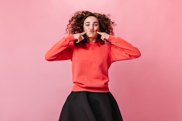 Positieve vrouw in oranje sweatshirt maakt grappig gezicht op roze achtergrond