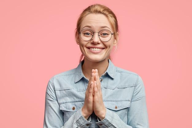 Positieve vrouw in spijkerjasje, drukt handpalmen tegen elkaar in boeddhistisch gebaar, buigt om vriend uit het buitenland te begroeten, bidt voor iets goeds, geïsoleerd over roze muur