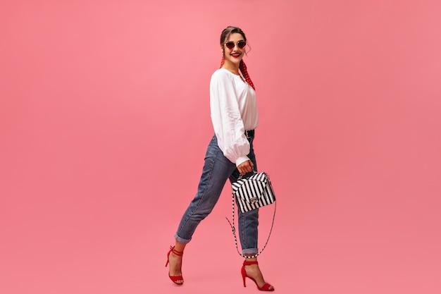 Positieve vrouw in stijlvolle outfit beweegt op roze achtergrond. mooie vrouw in witte blouse en rode hoge hakken lacht naar de camera.