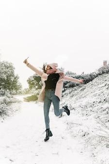 Positieve vrouw in warme kleren springen en zelfportret nemen op smartphone terwijl ze plezier hebben in de besneeuwde winterbossen