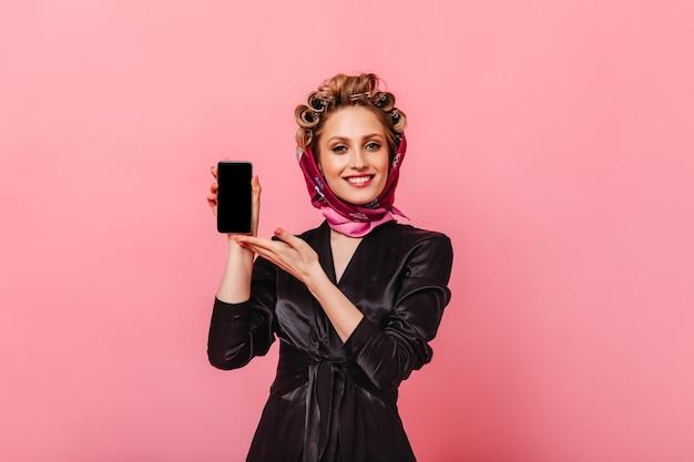 Positieve vrouw in zwarte mantel en sjaal demonstreert smartphone op roze muur