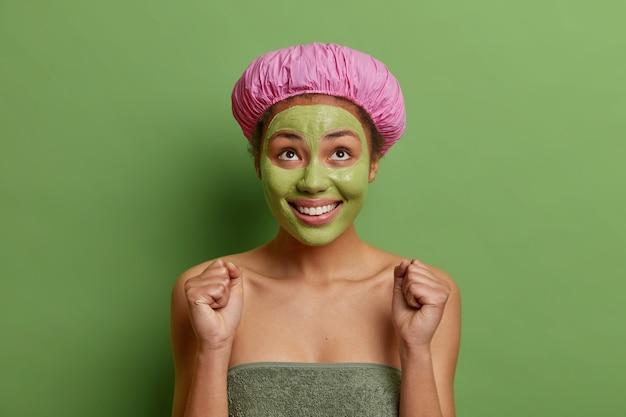 Positieve vrouw kijkt vrolijk boven gebalde vuisten wacht op iets speciaals draagt badmuts en handdoek rond lichaam past voedend avocado-masker toe op gezicht geïsoleerd op groene muur