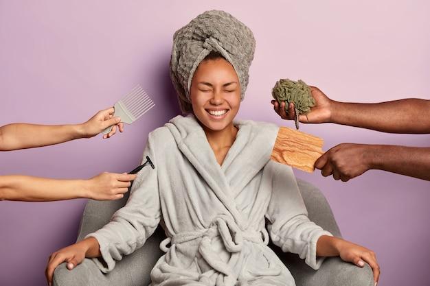 Positieve vrouw lacht oprecht, heeft een gladde, goed verzorgde huid, draagt een gewikkelde handdoek op het hoofd