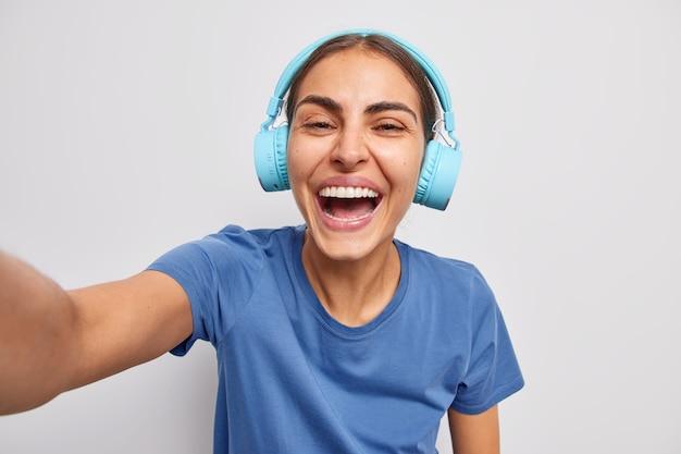 Positieve vrouw luistert naar muziek in draadloze hoofdtelefoons, nonchalant gekleed glimlacht breed en maakt een foto van zichzelf poseert over een witte muur