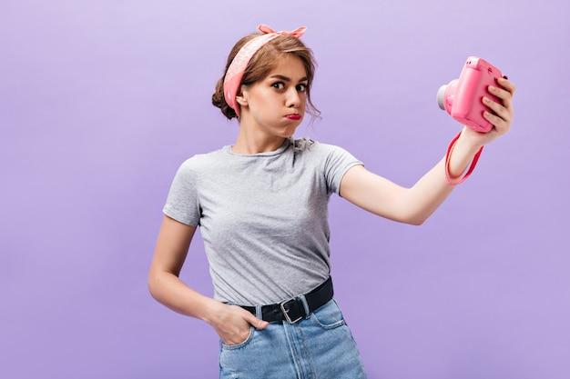 Positieve vrouw maakt grappig gezicht en houdt roze camera. cool jong meisje in trendy grijs t-shirt en denim huid met zwarte gordel poseren.