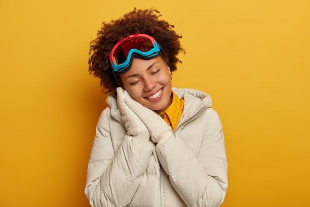 Positieve vrouw met afro-kapsel leunt tegen geperste handpalmen, heeft een dromerige gezichtsuitdrukking, draagt een witte jas, handschoenen en een snowboardmasker, geniet van winteravontuur, geïsoleerd op een gele muur.