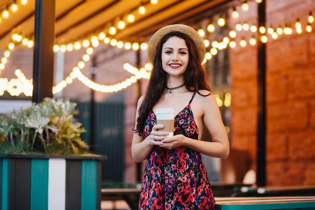 Positieve vrouw met donker haar en aantrekkelijk gezicht, zomerjurk en hoed dragen
