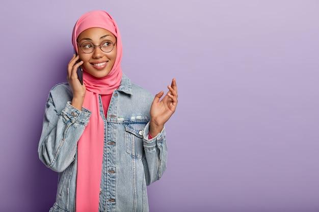 Positieve vrouw met donkere huid draagt traditionele moslim sjaal op het hoofd, houdt de mobiele telefoon bij het oor, geniet van een aangenaam gesprek, gebaren terwijl ze iets spannends vertelt aan de gesprekspartner geïsoleerd op paars