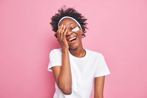 Positieve vrouw met donkere huidskleur heeft dolblij zorgeloze uitdrukking lacht om iets