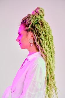 Positieve vrouw met dreadlocks onder kleurrijke lichten