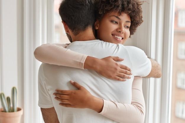 Positieve vrouw met een donkere huid omhelst haar man
