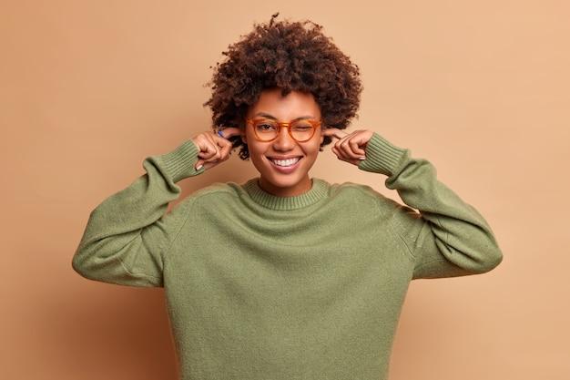 Positieve vrouw met gekrulde haren glimlacht vrolijk plugt oren vermijdt zeer luide muziek draagt een transparante bril en trui heeft een blij humeur geïsoleerd over bruine muur