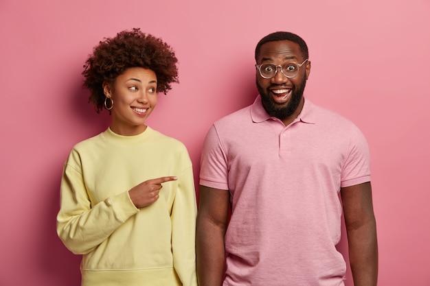 Positieve vrouw met gekrulde haren wijst naar grappige zwarte man