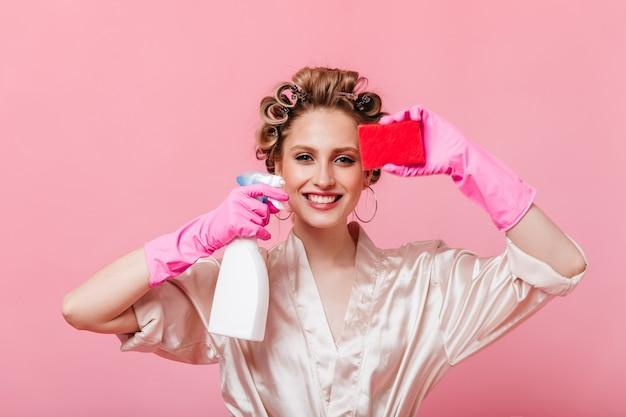 Positieve vrouw met haarkrulspelden houdt spons voor afwassen en spiegelreiniger