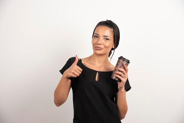 Positieve vrouw met kopje koffie maken duimen omhoog.