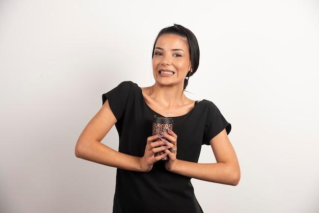 Positieve vrouw met kopje koffie staande op de witte muur.