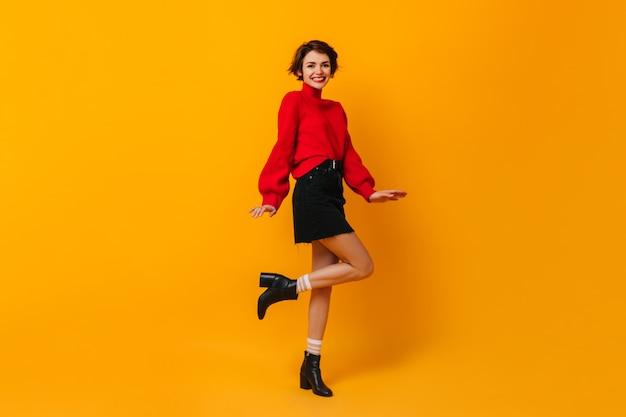 Positieve vrouw met kort haar die op gele muur dansen