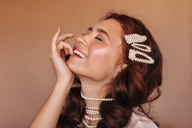 Positieve vrouw met krullend haar lacht en bijt op haar vinger. portret van vrouw met witte haarspelden en parelhalsband.