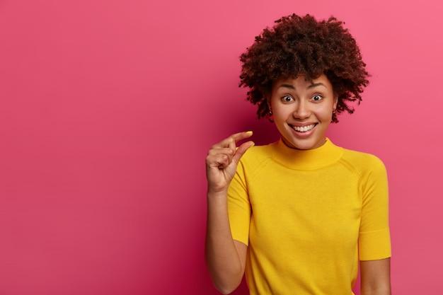Positieve vrouw met krullend haar meet een klein voorwerp, laat iets heel kleins zien