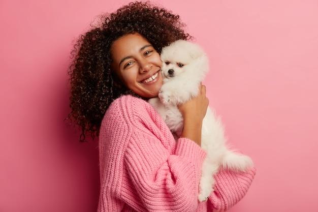 Positieve vrouw met krullend haar omhelst kleine puppy, drukt tedere gevoelens uit voor aaien, gekleed in gebreide trui, heeft bezoek gehad aan trimmer, poseert tegen roze achtergrond.
