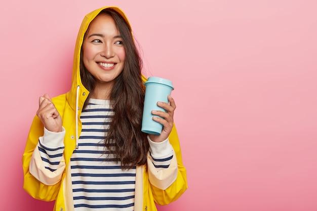 Positieve vrouw met lang donker steil haar, steekt gebalde vuist op, houdt afhaalkoffie vast, gekleed in gestreepte trui, gele regenjas