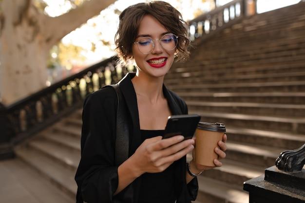 Positieve vrouw met rode lippen in zwarte outfit poseren met telefoon en kopje koffie. krullende vrouw die in glazen buiten glimlacht.