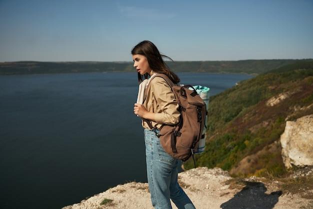 Positieve vrouw met rugzak die naar de rivier de dnjestr kijkt