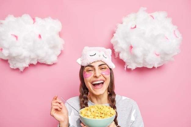 Positieve vrouw met twee staartjes glimlacht breed draagt slaappak en slaapmasker eet ontbijtgranen voor ontbijt geïsoleerd over roze muur