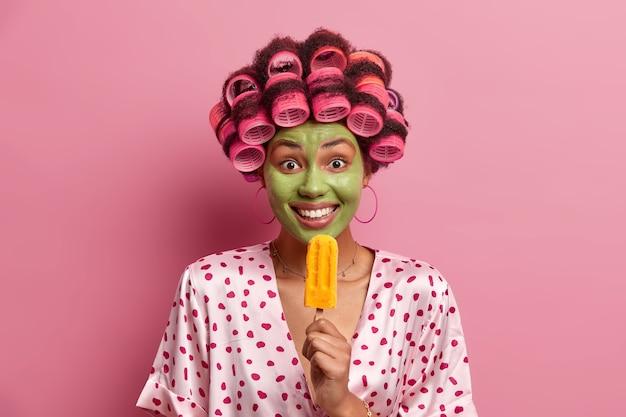 Positieve vrouw ondergaat schoonheidsprocedures, eet gele ijslolly, draagt haarkrulspelden voor het maken van perfect kapsel, geniet van heerlijk koud dessert, draagt ochtendjas, poseert tegen roze